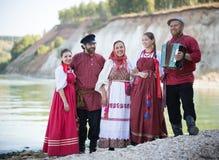 En grupp av härligt folk i det nationella ryska dräktanseendet på bakgrunden av vatten som ler arkivbild