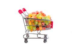 En grupp av kanderade frukter i en shoppingspårvagn Royaltyfri Foto