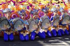 En grupp av karnevaldansare i olika dräkter dansar i fröjd längs gatan arkivfoto
