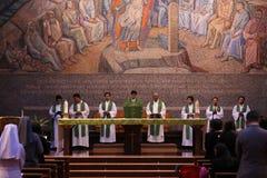 En grupp av katolska präster och systrar i den heliga massen royaltyfri bild