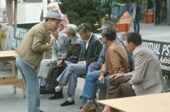 En grupp av kinesiska män som väntar på en hållplats, Royaltyfria Bilder