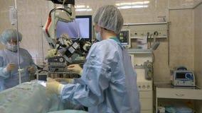 En grupp av kirurger i fungerande rummet att utföra mikroskopisk kirurgi på ENT organ genom att använda ett kirurgiskt mikroskop lager videofilmer