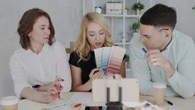 En grupp av kompetenta experter f?r en design antecknar en video kurs om nya trender i branschen Den blonda kvinnan talar lager videofilmer