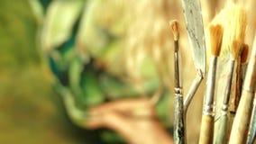 En grupp av konstmålarfärgborstar på bakgrund av arbete för yrkesmässig konstnär stock video