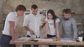 En grupp av kontorsarbetare som arbetar på ett utkast, övertids- teamwork stock video