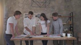 En grupp av kontorsarbetare som arbetar på en teckning, på övertid stock video