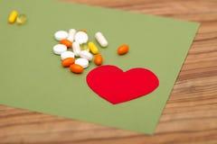 En grupp av kulöra piller och en röd hjärta på en grön bakgrund på tabellen royaltyfri bild