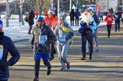 En grupp av löpare i dräkterna av olika tecken som kör längs stadsgatan under en halv maraton Arkivfoto