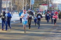 En grupp av löpare i olika dräkter som kör längs vinterstadsgatan under en halv maraton Royaltyfri Bild