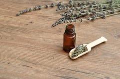 En grupp av lavendel med en träskopa fyllde med lavendel och en liten brun flaska Arkivfoton