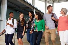 En grupp av lyckliga lärare som går i en skolakorridor fotografering för bildbyråer