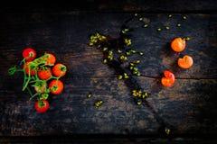 En grupp av nya röda tomater på det gamla mörka trägolvet Arkivfoto