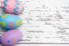 En grupp av pastell färgade påskägg på en vit träbakgrund arkivbilder