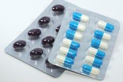 En grupp av pills och en grupp av kapslar Royaltyfria Foton