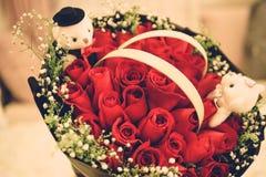En grupp av röda rosor och ett par av björndockor royaltyfri bild