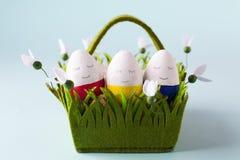 En grupp av roliga färgrika ägg i en korg - ett begrepp av den glade påsken, roliga tecken, sinnesrörelser Arkivfoton