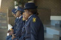 En grupp av söder - afrikanska poliser som i rad sitter Arkivbilder