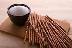 En grupp av salta brödpinnar och bunken av salt på träbakgrunden Royaltyfri Bild