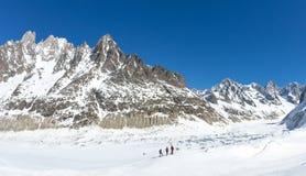 En grupp av skidåkare ser den Leschaux glaciären, i den Mont Blanc massiven, det högsta berget i Europa Royaltyfri Foto