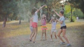 En grupp av små flickor som har gyckel och, kastar sig med kulör Holi pulverfestival av färger Holi lager videofilmer