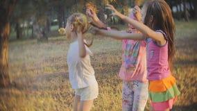 En grupp av små flickor som har gyckel och, kastar sig med kulör Holi pulverfestival av färger Holi stock video
