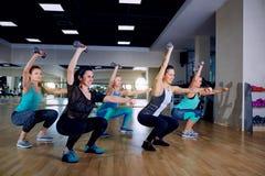 En grupp av sportflickor som gör sitta-UPS med hantlar i idrottshallen royaltyfri fotografi