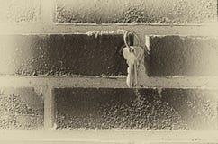 En grupp av tangenter som hänger på en tegelstenvägg med murbruk, tände, vid glidet fotografering för bildbyråer