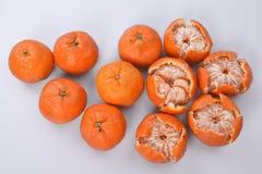 En grupp av tangerin på en vit bakgrund: vänstra mandariner i tjock apelsinskal, på den rätt halva-skalade frukten Royaltyfria Bilder