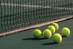 En grupp av tennisbollen på en domstol med netto i bakgrund royaltyfri bild