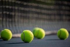 En grupp av tennisbollen p? en domstol med netto i bakgrund arkivfoto