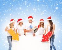 En grupp av tonåringar i julhattar som pekar på ett baner Arkivfoto