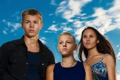 En grupp av tre tonåringar på den målmedvetna stranden Royaltyfria Bilder