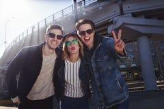 En grupp av tre vänner som har roligt och skrattar på gatan Fotografering för Bildbyråer