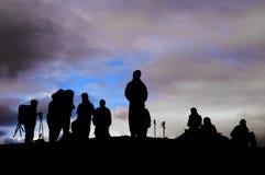 En grupp av trekkers svärtar konturn i bakgrunden för molnig himmel royaltyfri foto