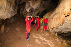 En grupp av turisten i en grotta Arkivbild