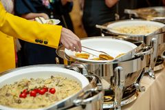 En grupp av turister äter middag alfreskomålningen En kvinna lägger mat bufferten arkivfoton