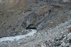 En grupp av turister går vidare en kall bergflod från en glaciär på monteringen Ushba i den Svaneti regionen fotografering för bildbyråer