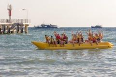 en grupp av turister på havet som sitter på en uppblåsbar banan och vinkar deras händer arkivfoto