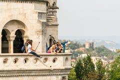 En grupp av unga caucasian manliga och kvinnliga turister som står på en synvinkel utanför och nedanför Matthias Church i Budapes Arkivfoto