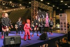 En grupp av unga dansare i ljuset av soffits Royaltyfri Bild