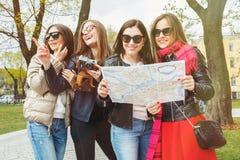 En grupp av unga kvinnliga turister s?ker efter dragningar i en europeisk stad p? ?versikten H?rliga fyra som ?r gladlynta och arkivfoto