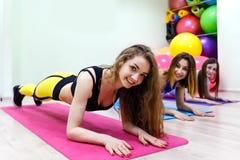 En grupp av unga kvinnor som gör övningsplankan i en konditionklubba royaltyfri fotografi