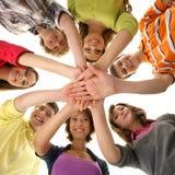 En grupp av unga teenages som tillsammans rymmer händer Royaltyfri Fotografi