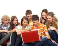 En grupp av unga tonåringar som ser bärbar dator Arkivfoto