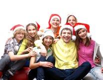 En grupp av unga tonåringar i julhattar Royaltyfri Fotografi