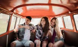 En grupp av unga vänner på en roadtrip till och med bygd som sitter i en minivan royaltyfri foto