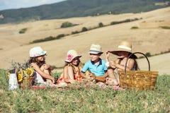 En grupp av 4 ungar som har en picknickdag Royaltyfria Bilder