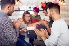En grupp av ungdomarmed födelsedagkakan inomhus fotografering för bildbyråer