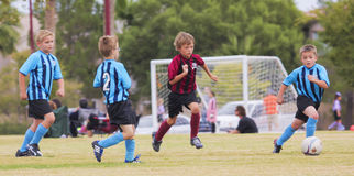 En grupp av ungdomfotbollspelare konkurrerar Arkivfoton
