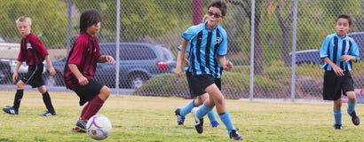 En grupp av ungdomfotbollspelare konkurrerar Royaltyfria Bilder